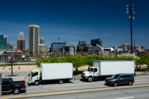 Image of trucks driving near the Baltimore skyline